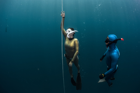ascend: Two lady free diver ascending along the rope in the depth Stock Photo
