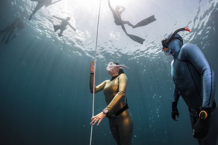 ascend: Lady free diver ascending along the rope in the depth
