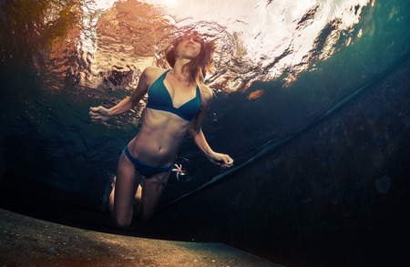 wet bikini: Underwater shot of young lady swimming in the pool
