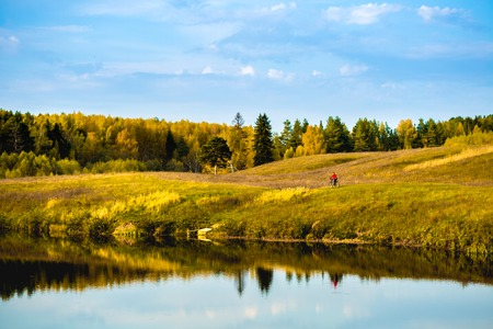 far off: Lady cycling on the autumn meadow near the lake at sunny day Stock Photo