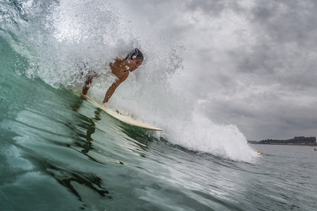 INDONESIA, BALI, CANGGU - NOVEMBER 25 2016: Young surfer catching the wave in the ocean