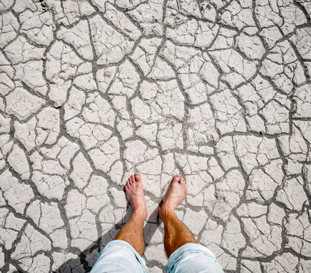 dryness: Man standing on the cracked ground of the Death Valley National Park, USA