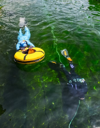 freediving: Free divers training with buoy in the swimming pool with green moss bottom
