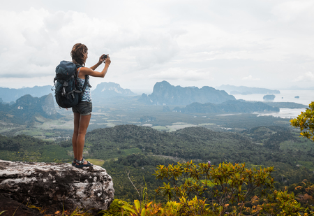 photo edges: Young lady hiker with backpack standing on top of the mountain and taking a picture of valley