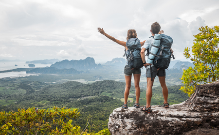 two on top: Hikers with backpacks relaxing on top of a mountain and enjoying the view of valley Stock Photo
