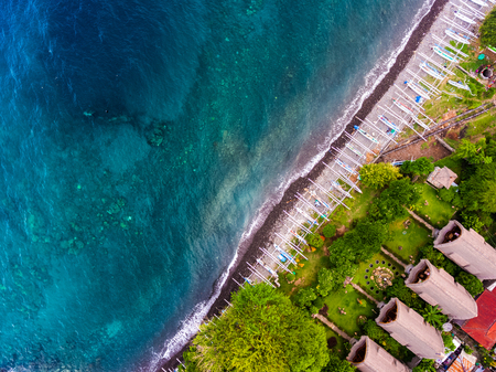 sunk: Aerial shot of Japanese ship wreck sunk near the coast. Traditional boats on the beach and green garden with bungalows on the land, Bali island, Indonesia