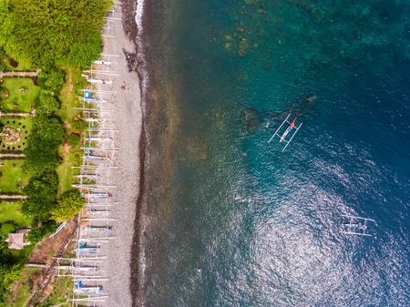 ship wreck: Aerial shot of Japanese ship wreck sunk near the coast. Traditional boats on the beach and green garden with bungalows on the land, Bali island, Indonesia