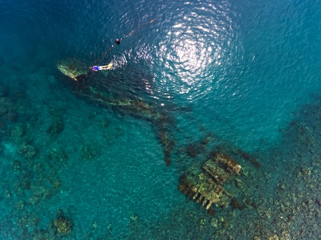 ship wreck: Aerial shot of the Japanese ship wreck with people snorkeling over it. Bali, Indonesia