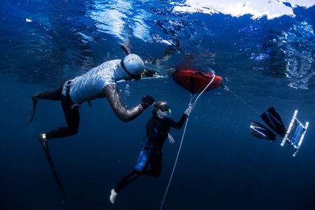 Free diver ascending along the rope Stock Photo