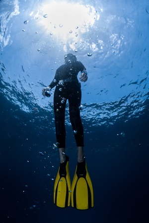 freediving: Underwater shot of the ascending free diver. Free immersion discipline