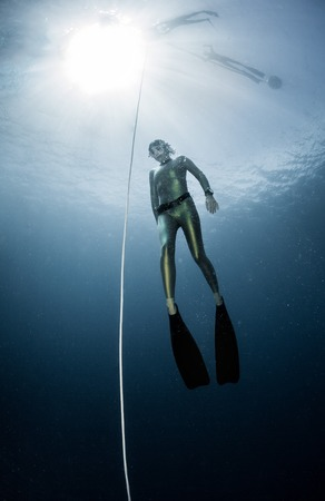 immersion: Underwater shot of the ascending free diver. Free immersion discipline