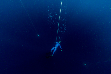 Free diver making air bubbles ring deep underwater
