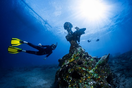reef: Free diver exploring the underwater statue in a tropical sea