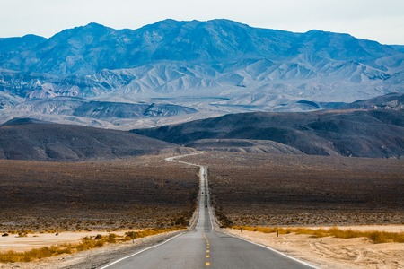 Road in the Death Valley National Park with mountains on the horizon. USA Stock Photo