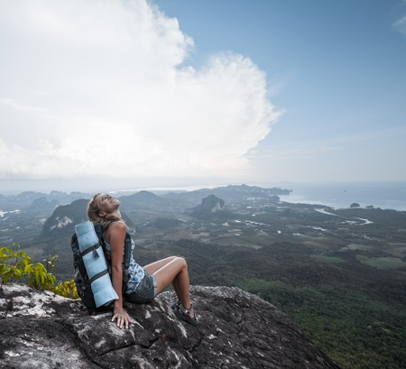 viewpoints: Young woman with backpack sitting on a cliff and enjoying a the view of valley