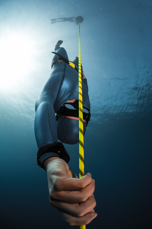 Free diver descending along the rope into depth. Free immersion discipline of the sport