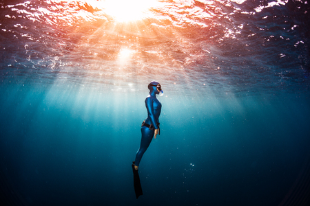 Woman free diver ascending from the depth in a tropical clear sea