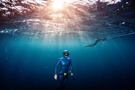 熱帯の澄んだ海の深さから上昇女性フリーダイバー