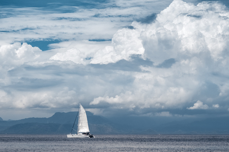 sailing boats: Sail boat moves in the sea with clouds and mountains on the background