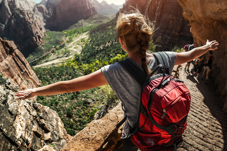 standing stones: Woman hiker standing with raised hands and watching valley view of Zion National Park, USA Stock Photo