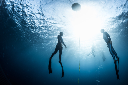 Two free divers, man and woman, ascending from the depth Stock Photo