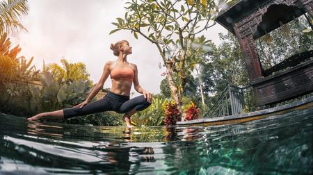 Jeune femme exécute exersises de yoga dans le jardin tropical de la piscine Banque d'images - 71797267