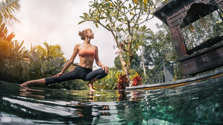 Young woman performs yoga exersises in the tropical garden by the pool Standard-Bild