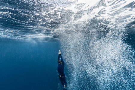 water bubbles: Free diver ascending from the depth in a rough sea with lots of bubbles. Stock Photo