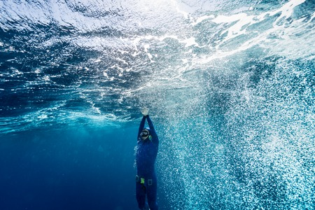 Free diver ascending from the depth in a rough sea with lots of bubbles. Stock Photo