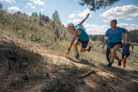off road: Trail running athletes crossing off road terrain at sunny day Stock Photo