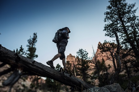 Hiker crossing rocky terrain in the Bryce canyon, USA