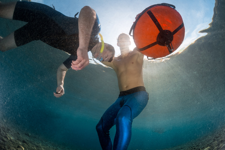Underwater shot of free divers training in low water in the tropical sea, Amed, Indonesia