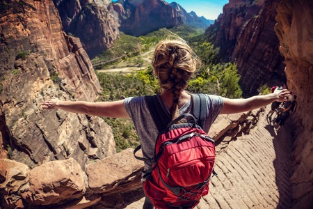 travel woman: Woman hiker standing with raised hands and watching valley view of Zion National Park, USA Stock Photo