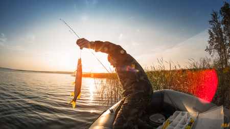 Man with fish in the boat on the lake at sunset Stock Photo