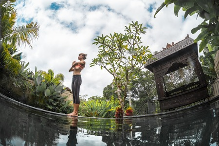 meditates: Young woman meditates in the tropical garden by the pool