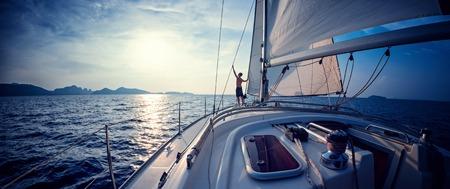 Jonge man die op het jacht in de zee bij zonsondergang