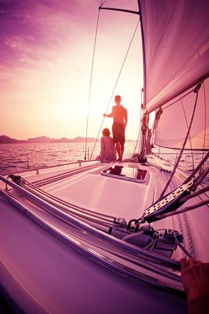海でセーリング ボートのデッキからの夕日を楽しむカップル