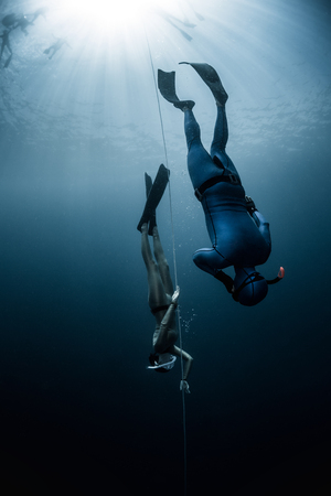 Free diver ascending along the rope in the depth Stock Photo