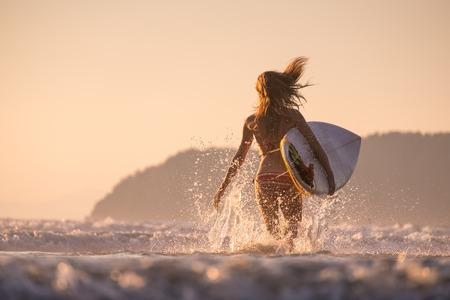 Frau läuft in den Ozean mit Surfbrett Standard-Bild