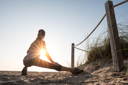 sitting on the ground: Woman performs stretching exercises on a beach at sunrise