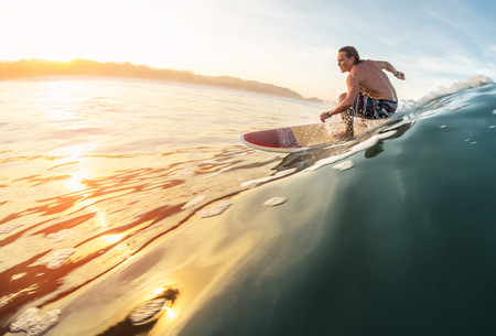 Surfer rides the perfect ocean wave at sunrise Stock Photo