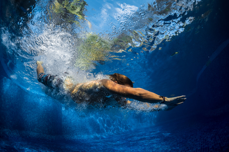 Underwater shot of the young man jumping in the pool Stock Photo
