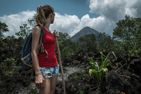 Young woman hiker standing on the trail and watching volcano on the horizon
