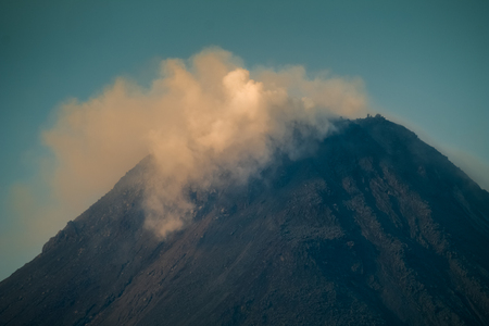 Summit of the active volcano of Arenal with smoke and clouds. Costa Rica