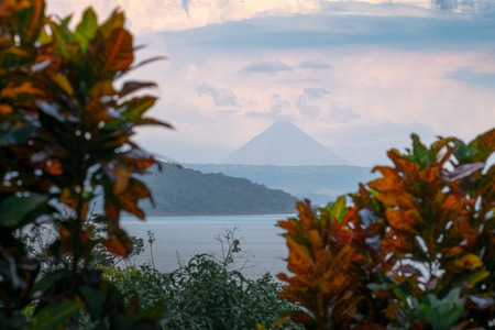 View of the volcano of Arenal with lush tropical trees on the foreground