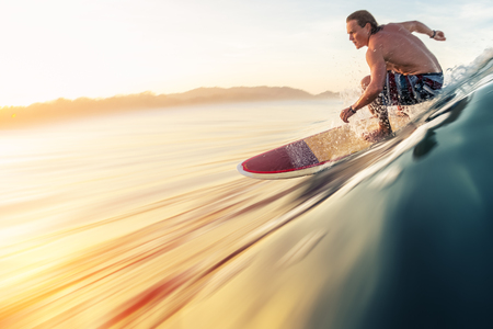 Surfer rides the perfect ocean wave at sunrise. Motion blurred water Stock Photo