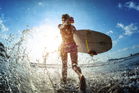 Young woman runs into the ocean with surfboard Zdjęcie Seryjne