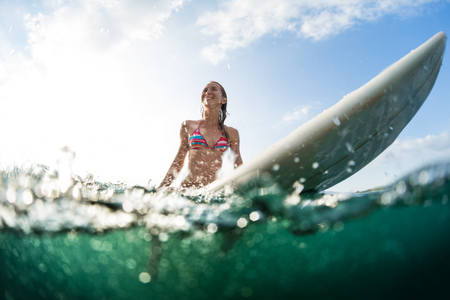 Happy woman sits on surfboard in an ocean