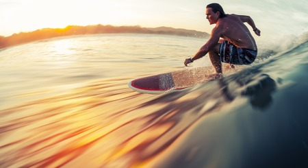 Surfer rides the ocean wave at sunrise Banque d'images