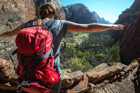 Hiker with backpack stands on the edge with raised hands and looks down at the valley Imagens